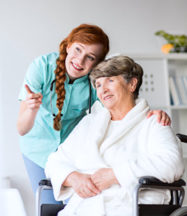 elder woman on wheelchair and caregiver