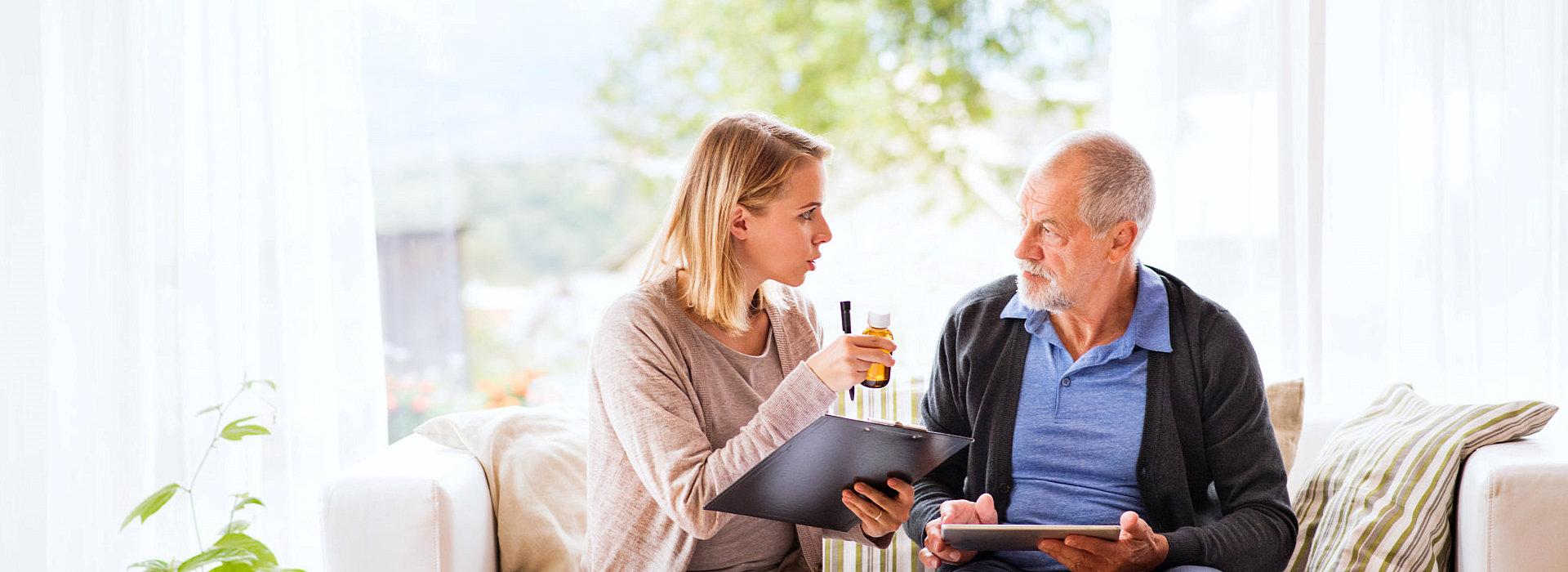 elder man and caregiver talking