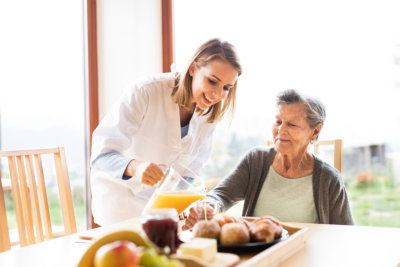 nurse giving food and drinks to senior woman