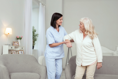 Cheerful caregiver helping senior woman who smiling